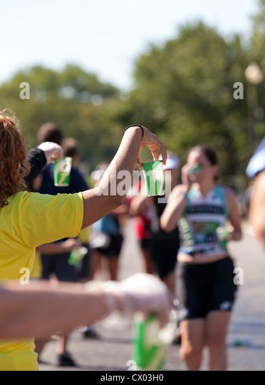 Marathon volunteer offering water to runners - Stock Image