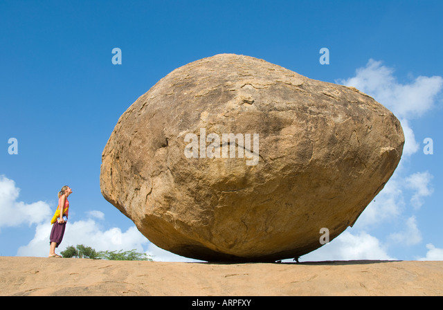 A tourist stands next to Krishna s Butterball in Mamallapuram in Tamil Nadu India - Stock Image