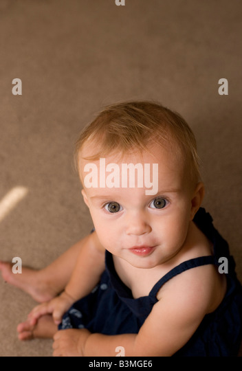 cute eight month old girl looking up at camera and smiling from a sitting position - Stock Image