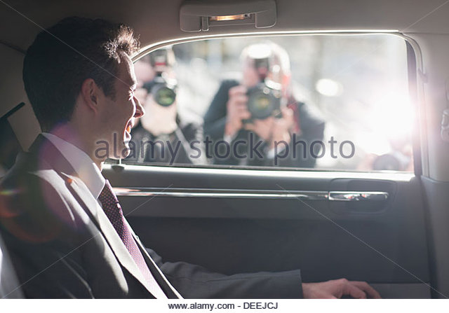 Politician smiling for paparazzi in backseat of car - Stock Image