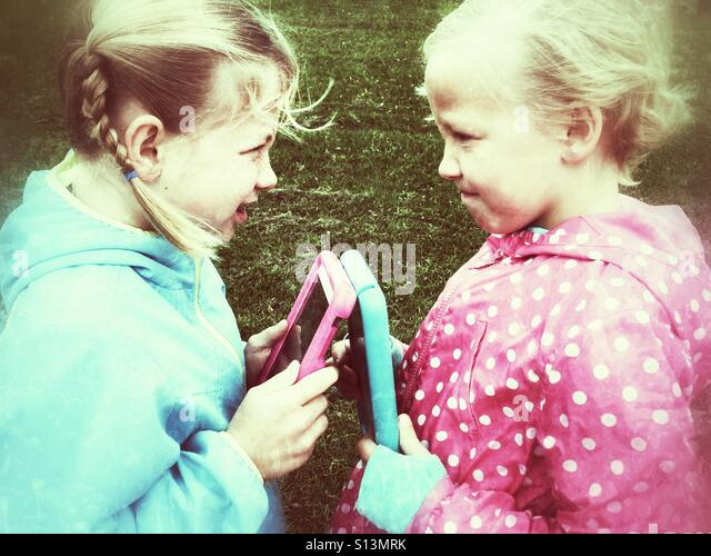 Girls face off over mobile devices. - Stock Image
