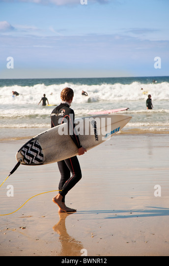 A surf enters the sea with his surfboard, Fistral Beach, Newquay, Cornwall, UK - Stock Image