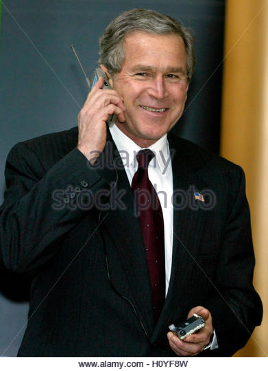U.S. President George W. Bush listens to a phone powered by hydrogen fuel cells at the National Building Museum - Stock Image