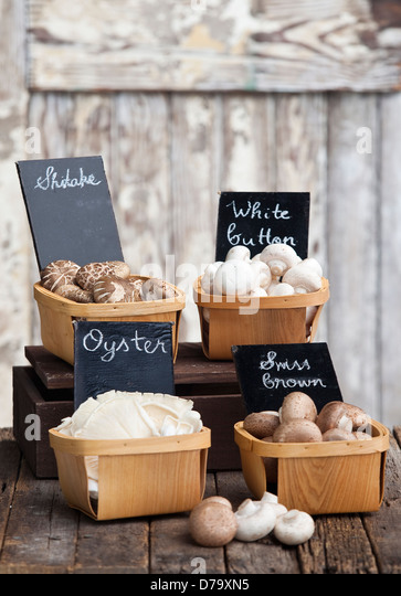 Punnets of Shitake, Swiss brown, Oyster and white button mushrooms on a rustic wooden tabletop. - Stock Image