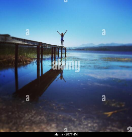 Young woman standing on edge of jetty - Stock Image