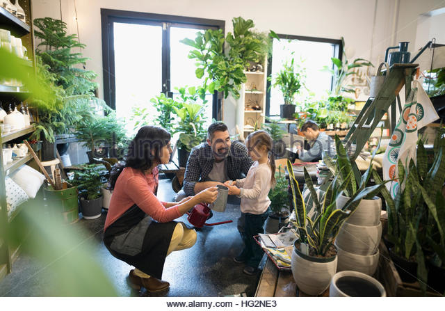 Female shop owner helping father and daughter shopping for watering cans in plant shop - Stock Image