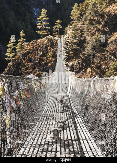 A suspended, prayer flag-covered bridge in the Himalayan Mountains of Nepal - Stock Image