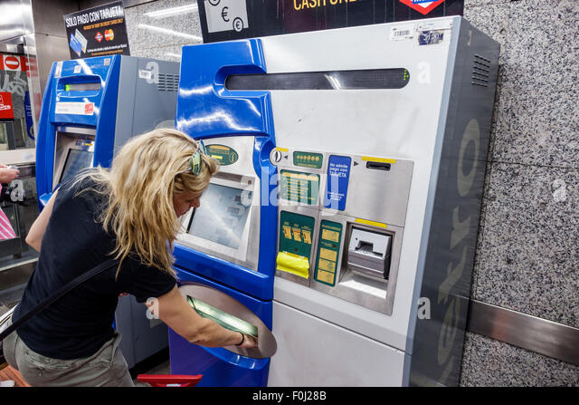 Spain Europe Spanish Madrid Banco de Espana Metro Station subway vending machine Hispanic woman buying ticket - Stock Image