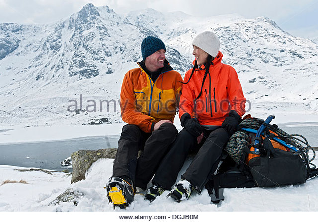 Climbing couple taking a break in front of snow covered mountains, Devils kitchen, llyn Idwal, Cwm Idwal, Snowdonia - Stock Image