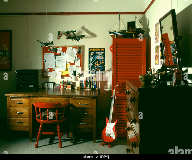 nineties study with old wooden desk and guitar leaning against red cupboard - Stock Image