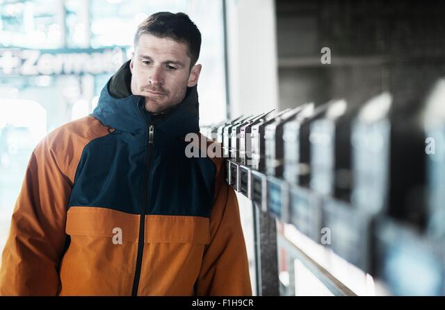 Mid adult man wearing coat, looking away - Stock Image