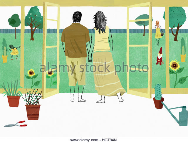 Couple holding hands looking out at daughters in garden from conservatory - Stock-Bilder