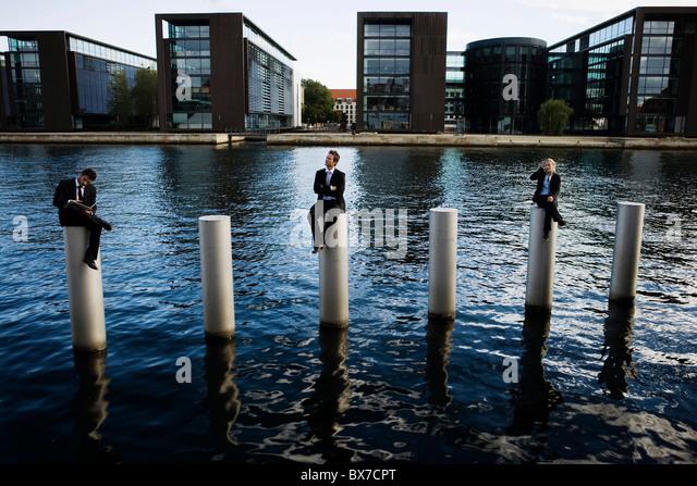 3 people sitting on poles - Stock Image