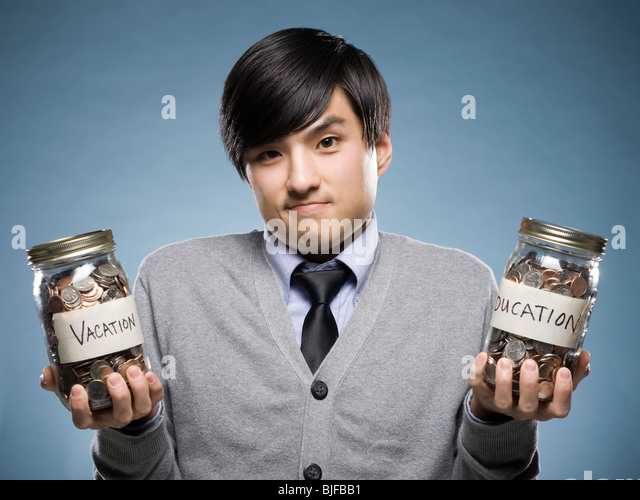 man holding two jars of coins - Stock Image