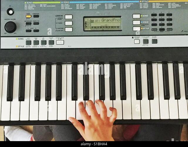 A child's hand playing a keyboard. - Stock Image