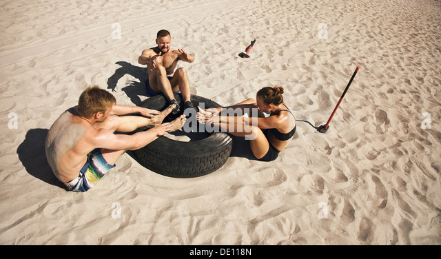 Fitness and healthy lifestyle. Small group of young athletes doing abdominal exercise with a truck tire on beach. - Stock-Bilder