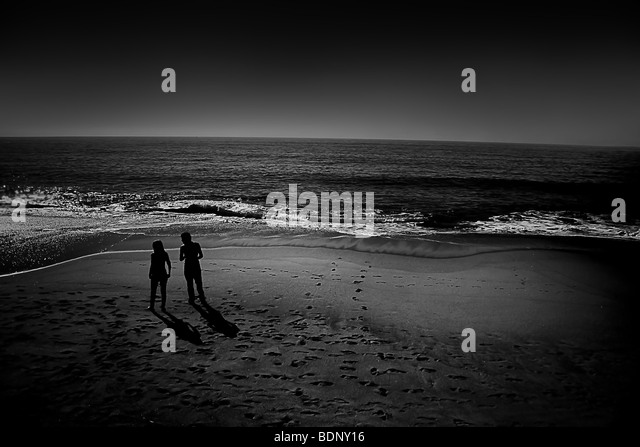 A couple silhouetted on a beach - Stock-Bilder