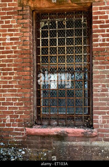 Rusty barred screened window. - Stock Image