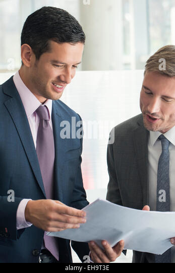 Business associates discussing document together - Stock Image