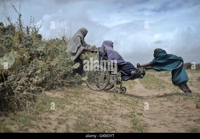 Two woman help another through a hedge of cactii at a food distribution center in Afgoye, Somalia, on August 4. - Stock-Bilder