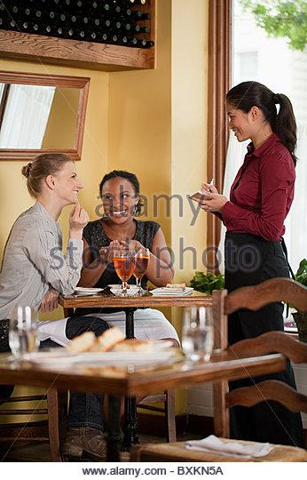 Waitress taking food order in restaurant - Stock Image