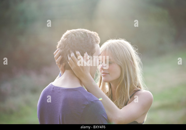 A romantic young couple embracing in the evening sun - Stock-Bilder