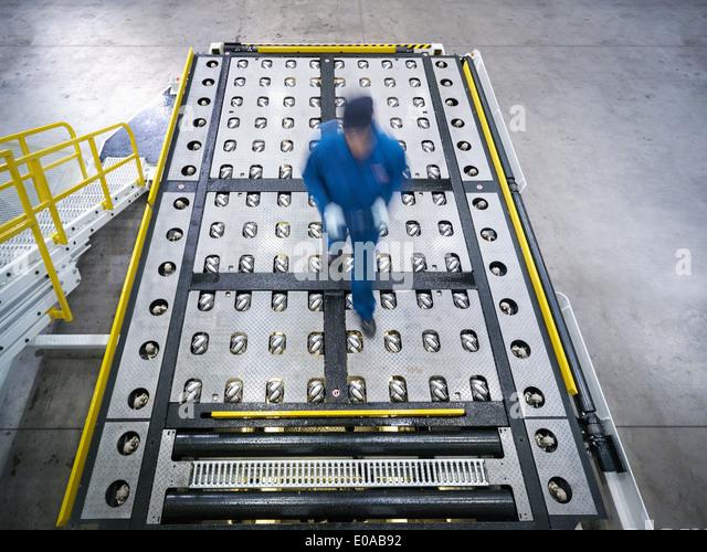 Engineer inspects baggage handling truck in truck repair factory - Stock Image