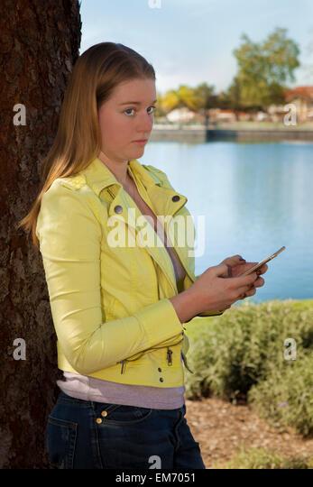 Caucasian 14-16 year old oldsTeenage girl using iPhone mobile phone device outdoors  MR  © Myrleen Pearson - Stock-Bilder