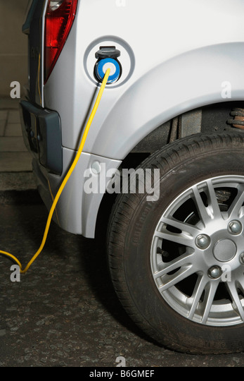 Electric cable attached to electric car - Stock Image