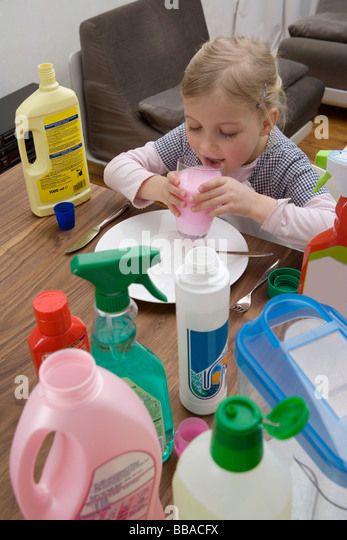 A young girl drinking cleaning fluid surrounded by medicines - Stock Image