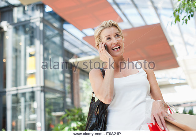 Woman carrying shopping bags and talking on cell phone - Stock Image