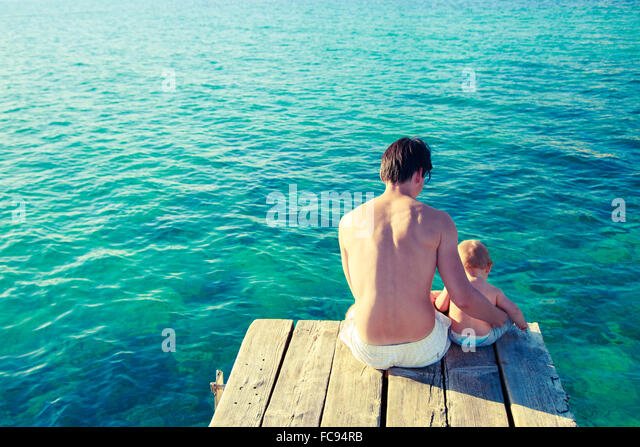 Young Father with His Son Relaxing by the Sea - Stock Image