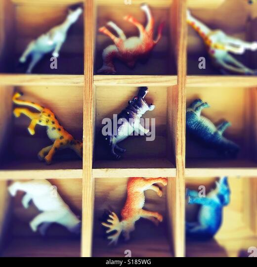 A hippo toys and other plastic animals in a wooden box. - Stock Image