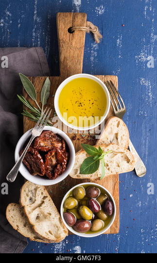 Mediterranean snacks set. Olives, oil, herbs and sliced ciabatta bread on yellow rustic oak board over painted dark - Stock Image