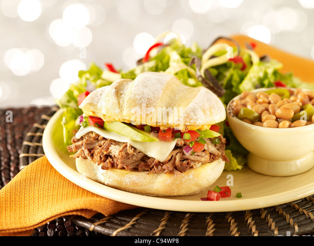 Pork sandwich on artisan bread served with side salad and pinto beans - Stock Image