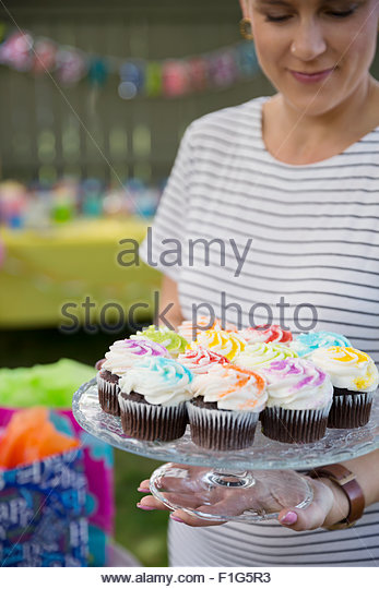Woman holding cupcakes on cake stand - Stock Image