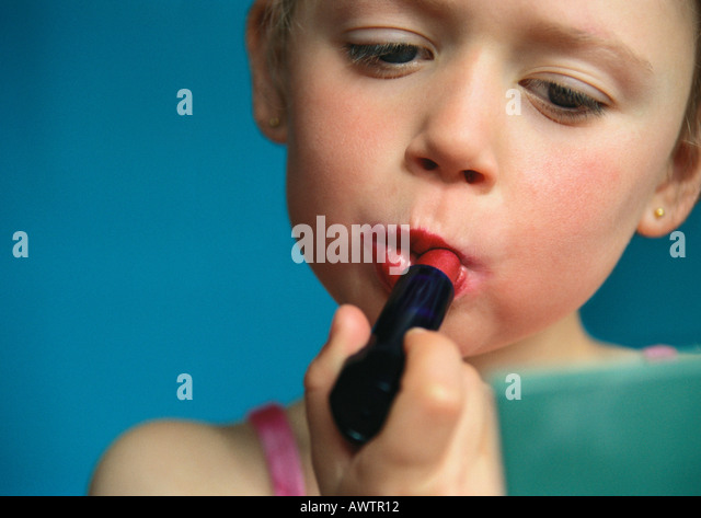 Little girl putting on lipstick, close-up - Stock Image