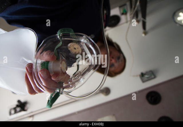 Female EMT giving patient oxygen in the back of an ambulance. - Stock Image