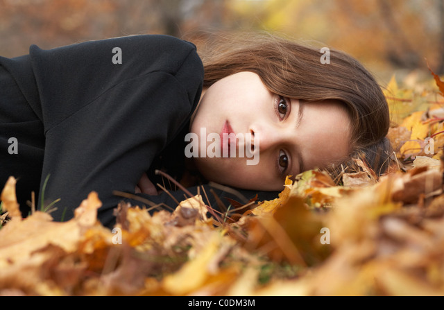 Child laying in fallen leaves - Stock Image