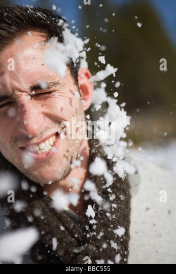 Man getting hit in face by snowball - Stock-Bilder