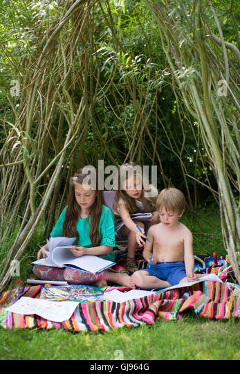 PROPERTY RELEASED. MODEL RELEASED. Children playing in a den in the garden. - Stock Image