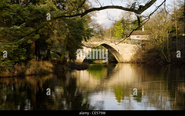 Froggatt Bridge reflected in the waters of the river Derwent at the village of Froggatt in the Derbyshire Peak District - Stock Image