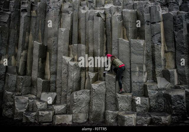Female tourist climbing up rock formation,  Reynisfjara, Iceland - Stock Image