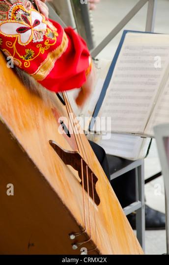 Ukraine, Yalta, Livadia Palace. Ukrainian folkloric show. Man playing large Russian three-stringed balalaika. - Stock Image
