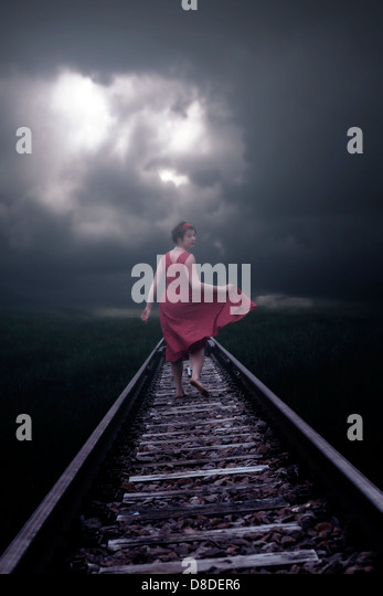 a girl in a red dress is running on railway tracks - Stock Image