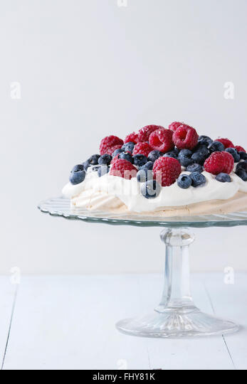 Vintage cake stand with Meringue dessert Pavlova with fresh blackberries and raspberries over blue wooden table. - Stock Image
