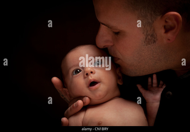 Happy Young Father Holding His Mixed Race Newborn Baby Under Dramatic Lighting. - Stock Image