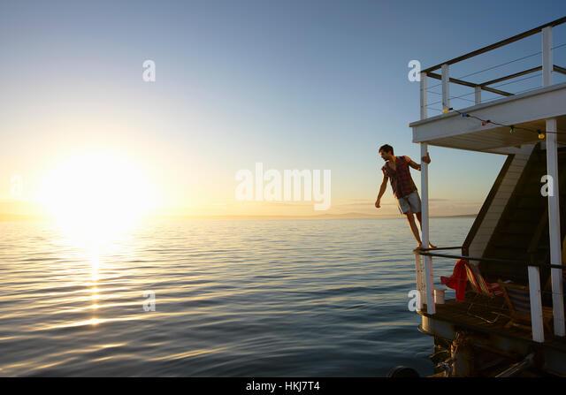 Man leaning on summer houseboat railing over sunset ocean - Stock-Bilder