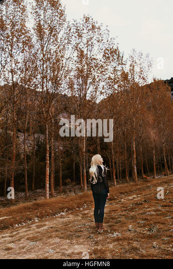 Young woman alone in a forest in autumn back at camera - Stock Image