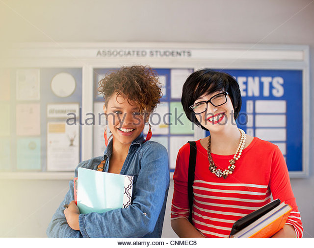 Students smiling together in hallway - Stock Image